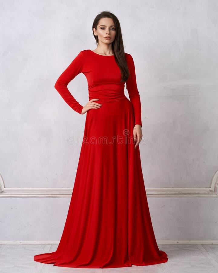 Mulher moreno nova no vestido de noite vermelho foto de stock