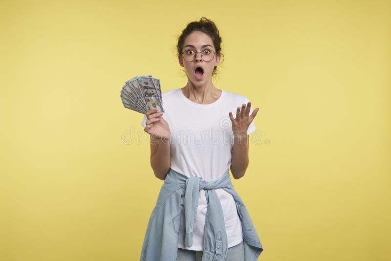 A mulher moreno nova pode o ` t acreditá-la ganhou uns lotes do dinheiro, abriu seus boca e olhos em uma surpresa imagem de stock