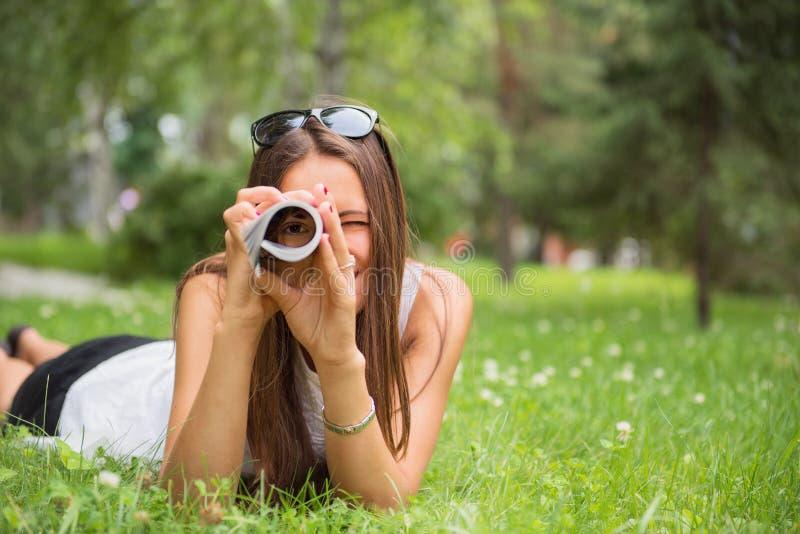 Mulher moreno nova que aprecia o encontro na grama verde fotos de stock