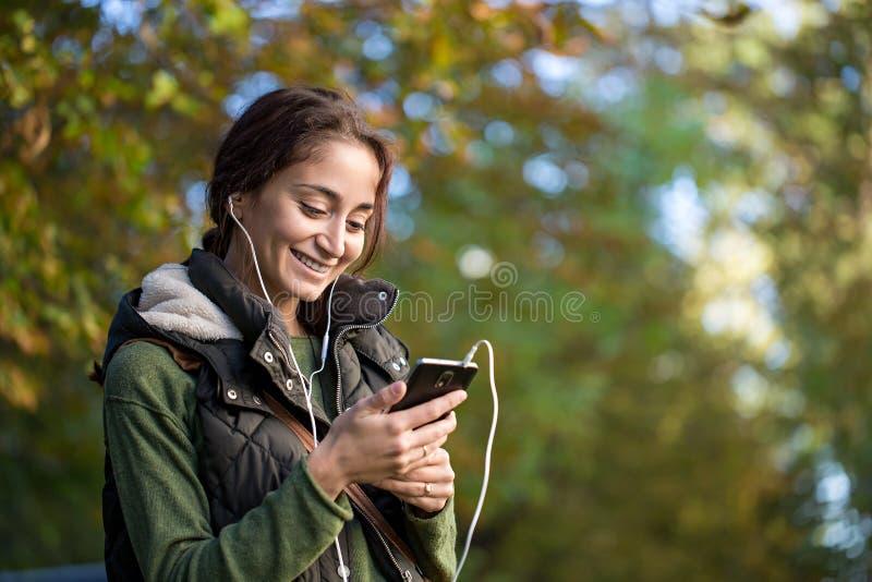 Mulher moreno nova que escuta a música no parque do outono imagens de stock