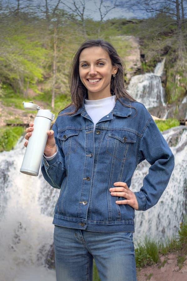 Mulher moreno nova que guarda a garrafa t?rmica branca Retrato da menina de viagem perto da cachoeira imagens de stock royalty free