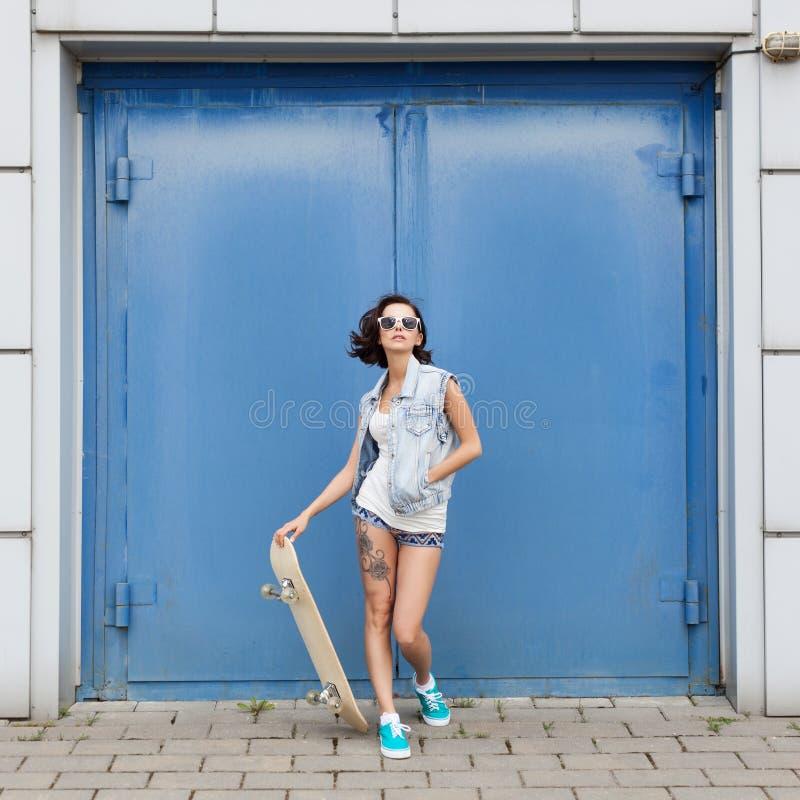 Mulher moreno nova que levanta com skate imagens de stock