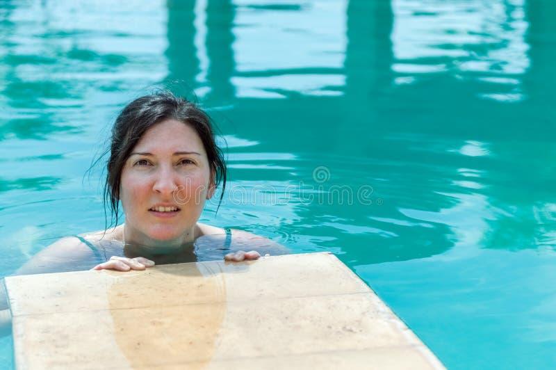 Mulher moreno nova que relaxa na piscina em um recurso foto de stock royalty free