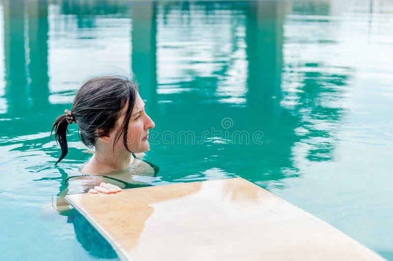 Mulher moreno nova que relaxa na piscina em um recurso imagens de stock
