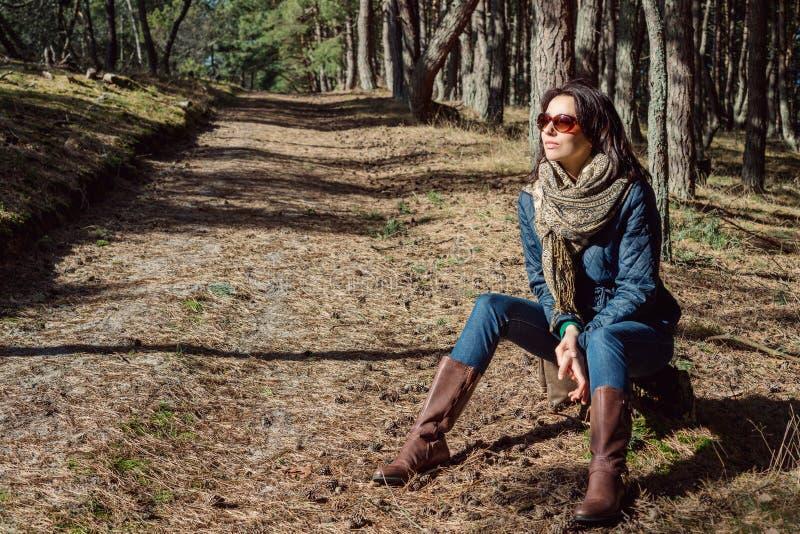 Mulher moreno nova que senta-se em um coto nas madeiras fotografia de stock royalty free