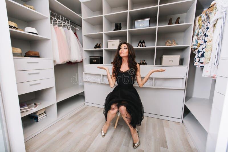 A mulher moreno nova que senta-se em um vestuário enorme pensa sobre a escolha da roupa, ela é preto à moda vestido fotografia de stock royalty free