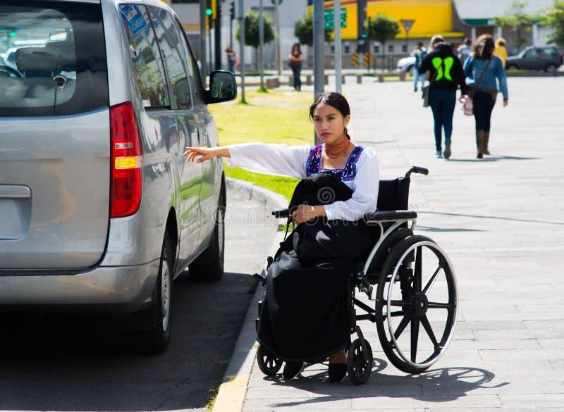 Mulher moreno nova que senta-se na cadeira de rodas que sorri com a atitude positiva, guardando para fora o braço que procura o t fotos de stock