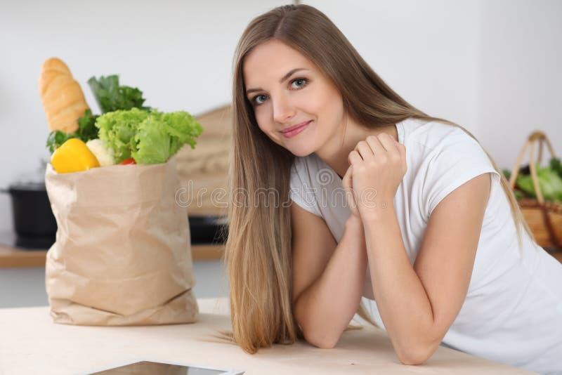 Mulher moreno nova que sorri ao sentar-se na tabela perto do saco de papel completamente de vegetais e de frutos Conceito do foo fotos de stock