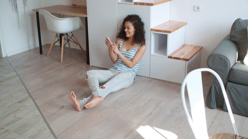 Mulher moreno nova que usa o telefone celular em casa imagens de stock