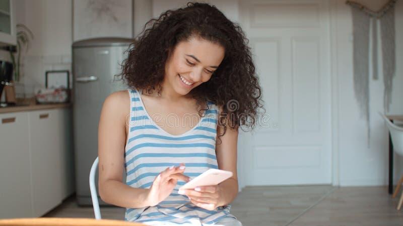 Mulher moreno nova que usa o telefone celular em casa foto de stock royalty free