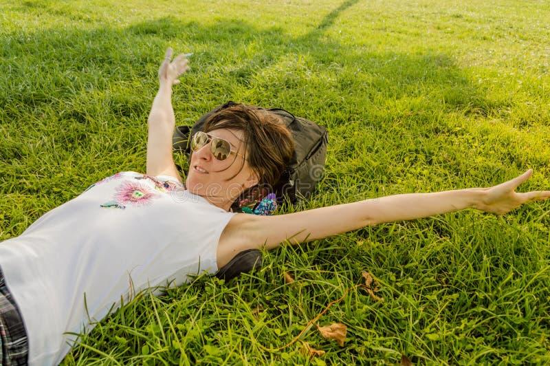 Mulher moreno que aprecia o encontro nela para trás na grama verde na natureza imagens de stock royalty free