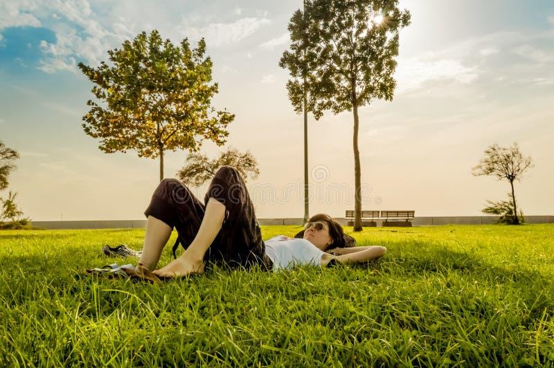 Mulher moreno que aprecia o encontro nela para trás na grama verde na natureza imagens de stock