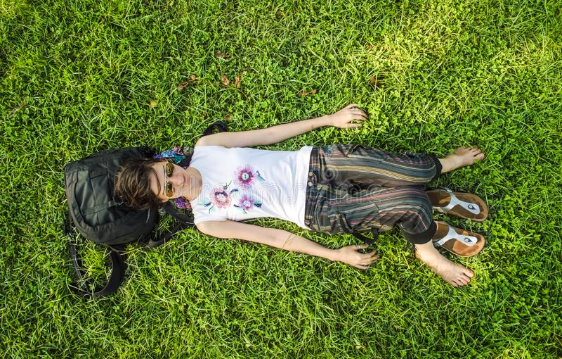Mulher moreno que aprecia o encontro nela para trás na grama verde na natureza imagem de stock