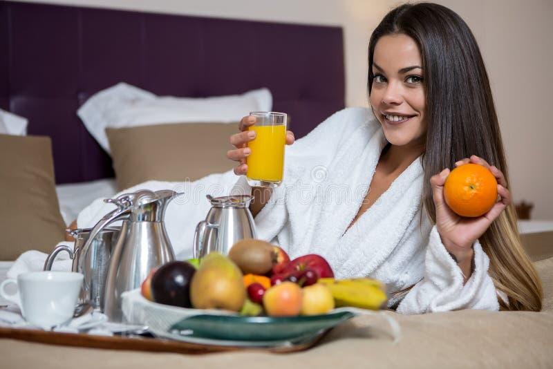 Mulher moreno que encontra-se na cama com suco de laranja imagens de stock