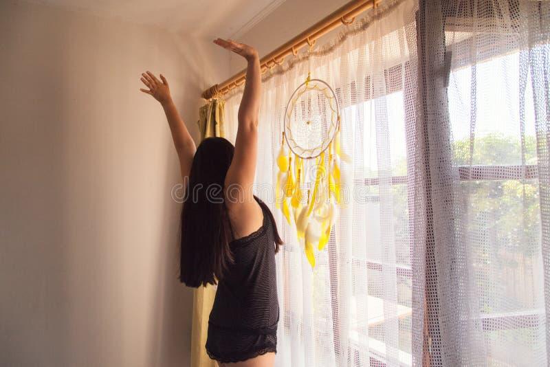 Mulher moreno que estica na manhã ao olhar fora da janela - vista traseira fotos de stock