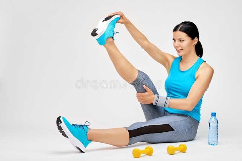 A mulher moreno que faz o esticão exercita no gym fotos de stock royalty free