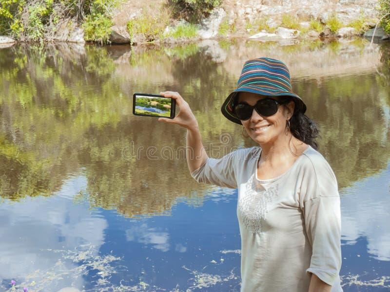 Mulher moreno que faz uma foto com seu telefone celular que olha a câmera imagens de stock