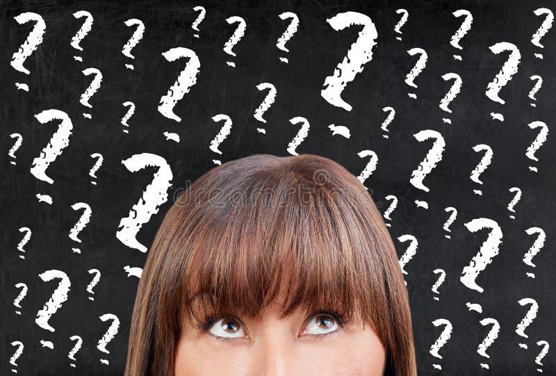Mulher moreno que pensa contra pontos de interrogação do quadro do quadro-negro fotografia de stock royalty free