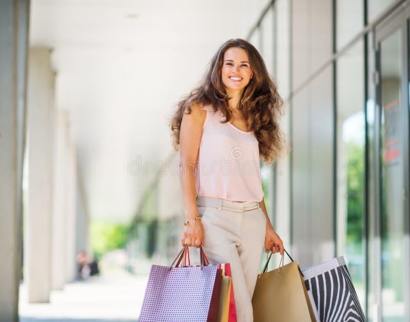 Mulher moreno que sorri sobre seu shopping spree bem sucedido imagens de stock