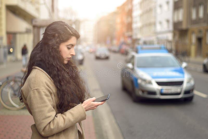 Mulher moreno que texting ao estar pela rua movimentada fotografia de stock