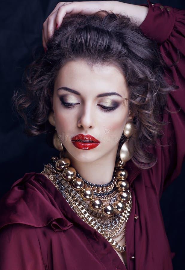 Mulher moreno rica com muita joia, composição vermelha latino-americano do batom do cabelo encaracolado foto de stock royalty free