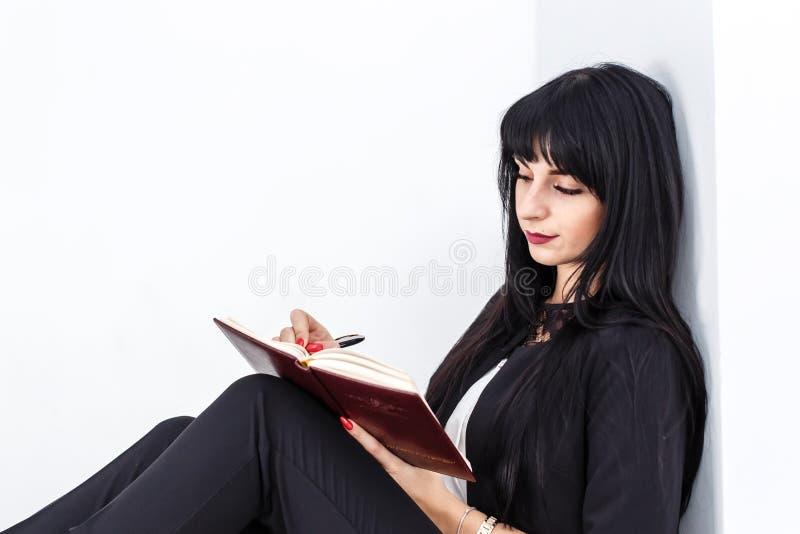 Mulher moreno séria atrativa nova vestida em um terno de negócio preto que senta-se em um assoalho em um escritório, escrevendo e fotos de stock