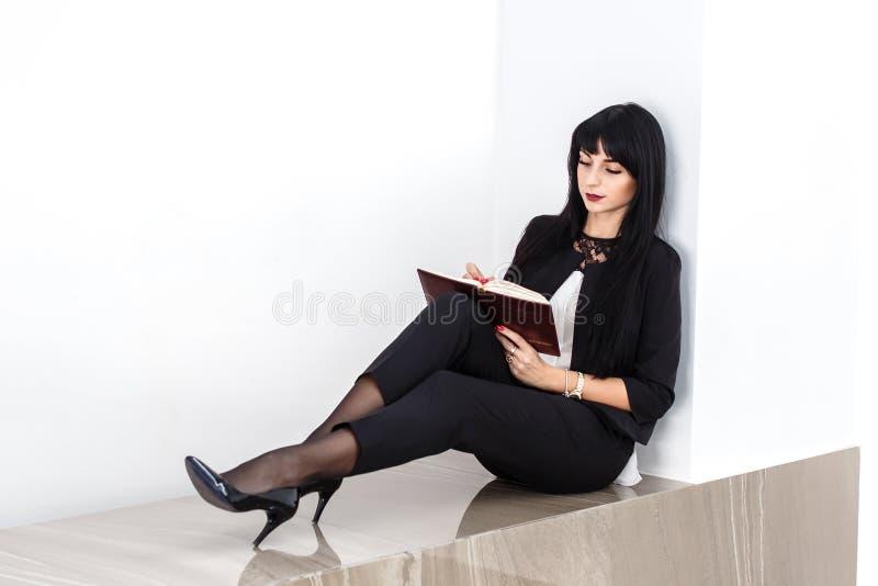 Mulher moreno séria atrativa nova vestida em um terno de negócio preto que senta-se em um assoalho em um escritório, escrevendo e imagens de stock