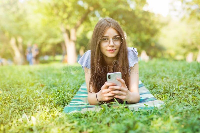 Mulher moreno satisfeito nos monóculos que encontram-se na grama e que usam o smartphone no parque fotografia de stock royalty free