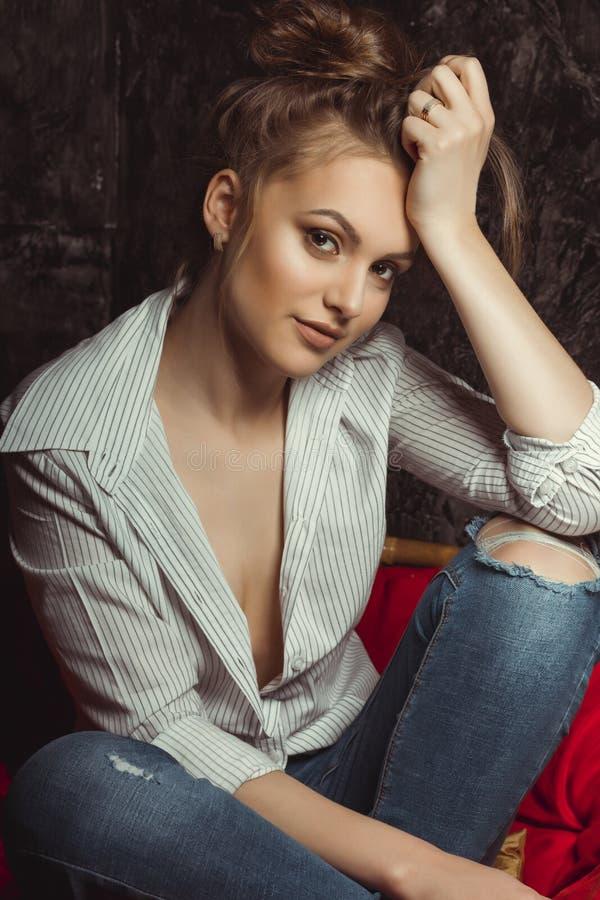 Mulher moreno sensual com composição natural na camisa e no jea rasgado fotografia de stock