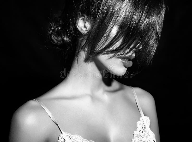 Mulher moreno 'sexy' bonito feliz bonita com os bordos vermelhos na roupa interior dos pijamas no fundo branco fotografia de stock royalty free