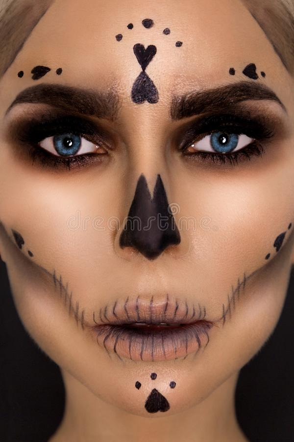 Mulher moreno 'sexy' do retrato na composição de Dia das Bruxas em um fundo preto no estúdio Prepare o esqueleto, o monstro e a b fotografia de stock royalty free