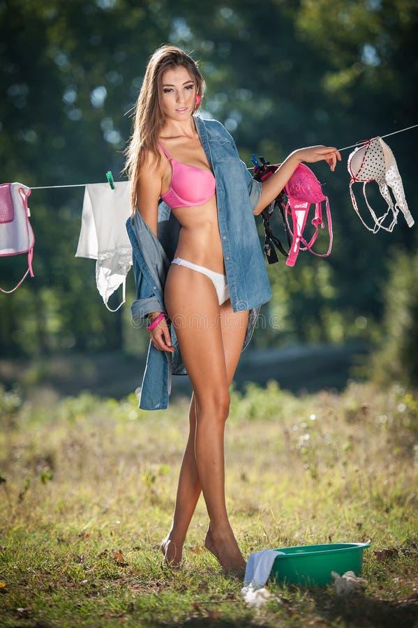 Mulher moreno 'sexy' no biquini e na camisa que põem a roupa para secar no sol Fêmea nova sensual com os pés longos que põem para imagens de stock