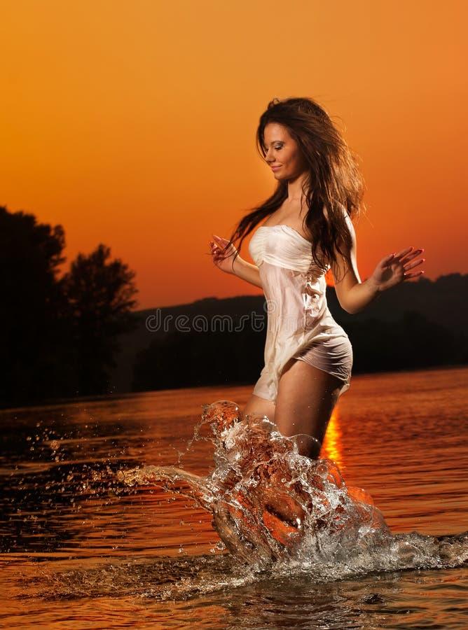 Mulher moreno 'sexy' no roupa de banho que corre na água do rio Jovem mulher 'sexy' que joga com água durante o por do sol Mulher foto de stock