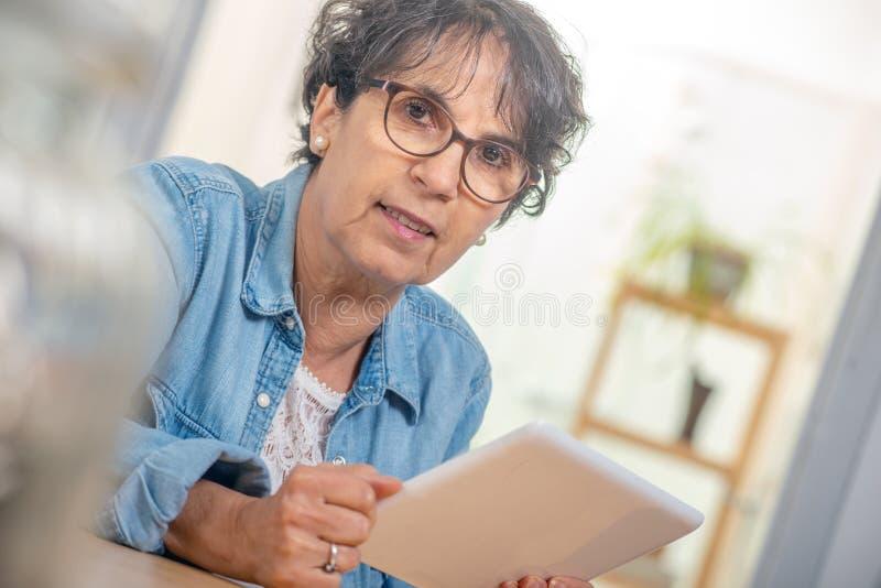 Mulher moreno superior de encantamento com vidros usando a tabuleta digital em casa imagem de stock royalty free
