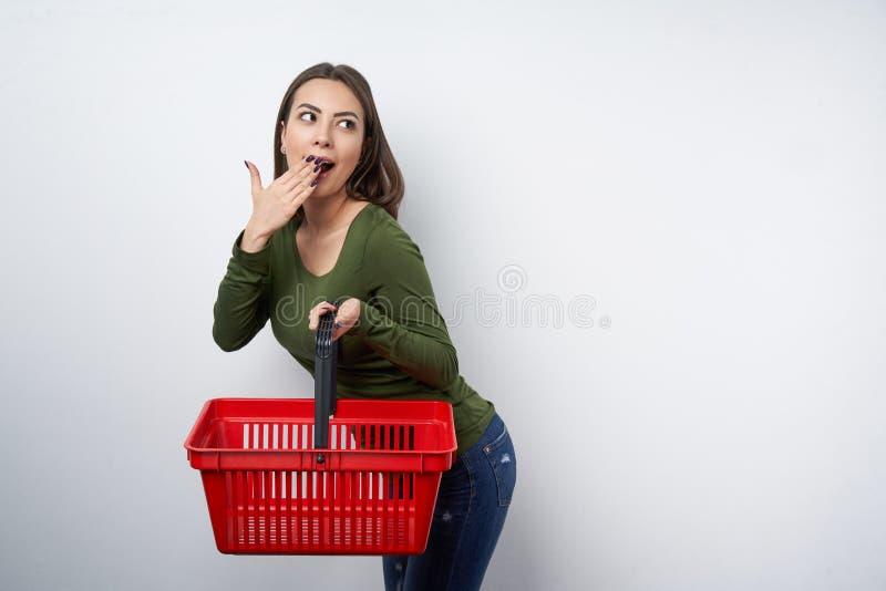 Mulher moreno surpreendida que guarda o cesto de compras vazio foto de stock