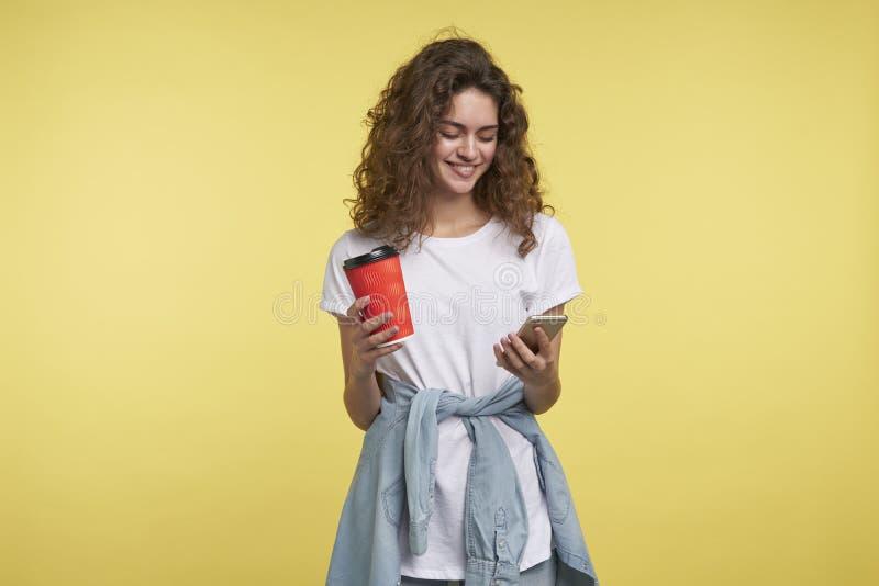 Mulher moreno tímida bonita que conversa através do mensageiro do whatsapp a que guarda o copo de café, um tiro isolado sobre o a foto de stock royalty free
