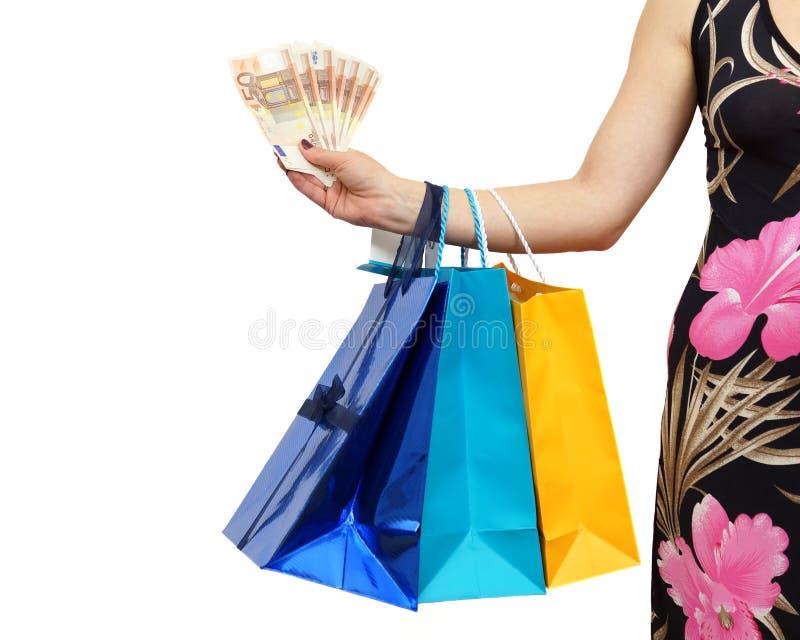 A mulher mostra economias do dinheiro com lote do al dos sacos de compras imagens de stock royalty free