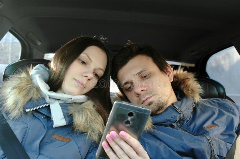 A mulher mostra a homem algo no telefone celular Estão para baixo nos revestimentos azuis que sentam-se no carro Front View imagem de stock royalty free