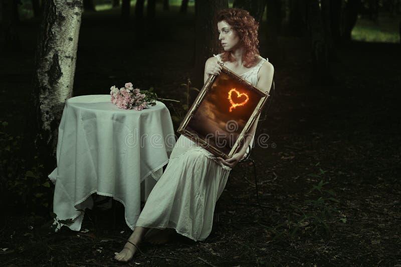 A mulher mostra-lhe coração ardente foto de stock