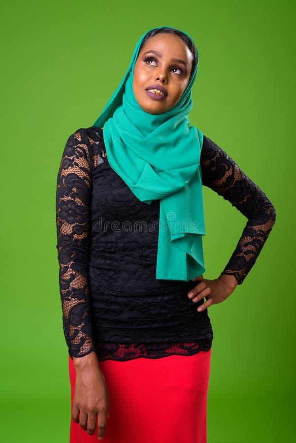 Mulher muçulmana africana nova contra a chave do croma com fundo verde fotografia de stock