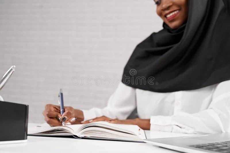 Mulher muçulmana africana nova que senta-se no local de trabalho, escrita imagens de stock royalty free