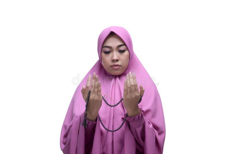 A mulher muçulmana asiática nova com os grânulos de oração que levantam a mão reza fotografia de stock