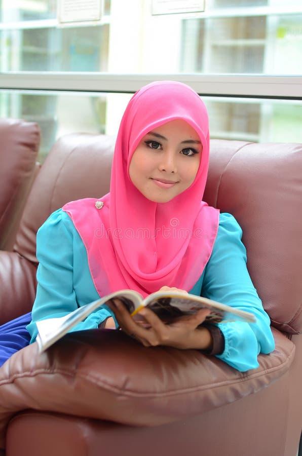 Mulher muçulmana asiática nova no compartimento principal da leitura do sorriso do lenço foto de stock
