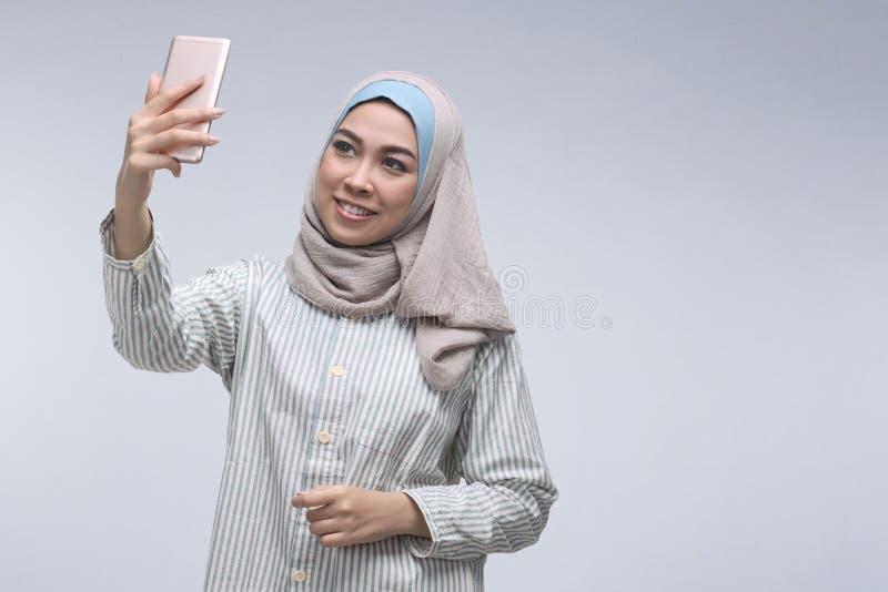 Mulher muçulmana asiática nova que levanta o selfie de fala com telefone celular imagem de stock royalty free