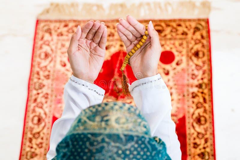 Mulher muçulmana asiática que reza com corrente dos grânulos imagens de stock
