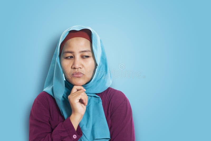Mulher muçulmana asiática que veste o hijab azul com expressão de pensamento, espaço da cópia Sobre o fundo azul fotos de stock