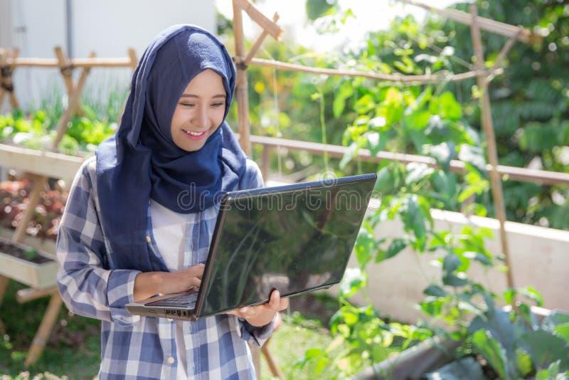 Mulher muçulmana atrativa com o portátil na exploração agrícola imagens de stock