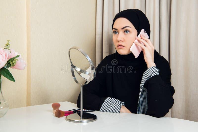 Mulher muçulmana bonita feliz alegre que senta e que usa o telefone celular móvel que chama para o amigo que conversa durante o f fotografia de stock royalty free