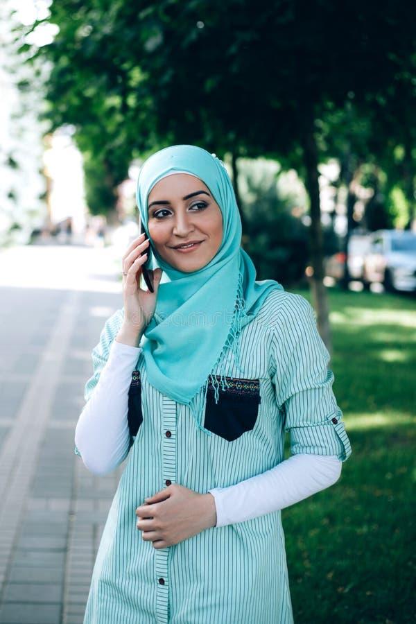 Mulher muçulmana bonita que fala pelo smartphone na rua imagens de stock