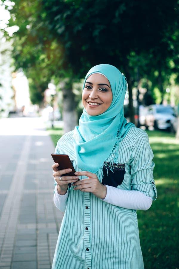 Mulher muçulmana bonita que usa o smartphone na rua fotos de stock royalty free